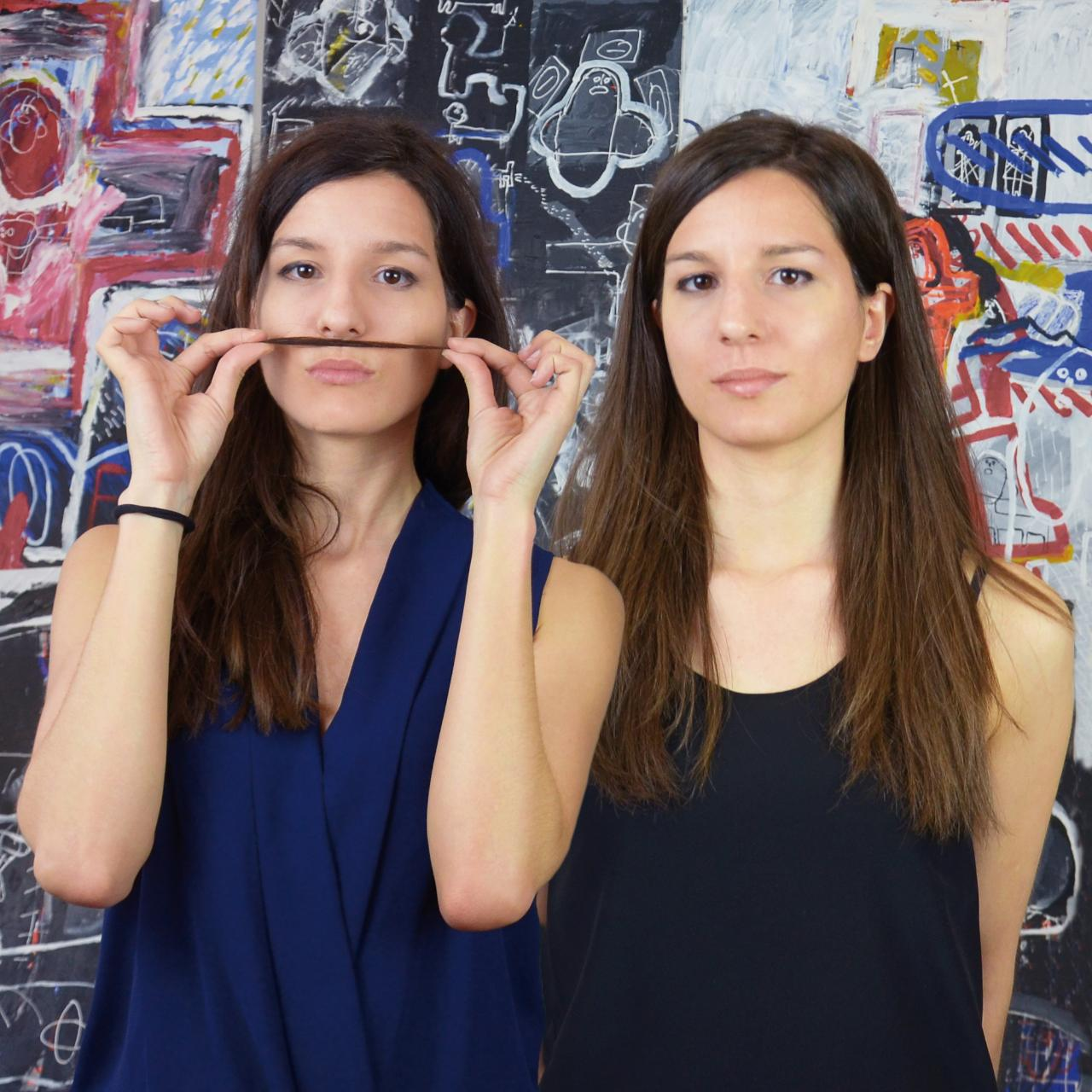 Eva Yarza, holding her hair as a mustache, and her twin sister Marta in their London design studio.
